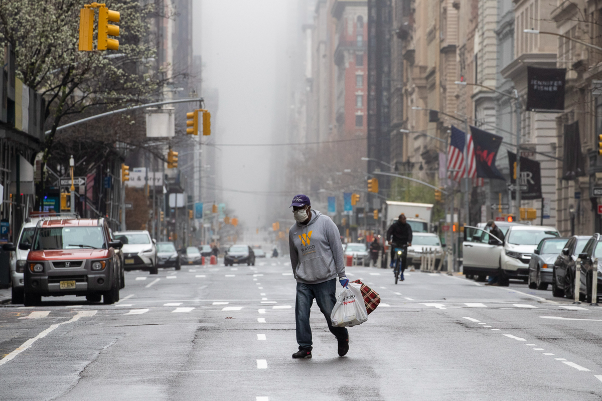A man wearing a facial mask walks across 5th Avenue in Midtown Manhattan. Americans are now being asked to prepare for at least another 30 days of severe economic and social disruption. [Mary Altaffer/AP Photo]