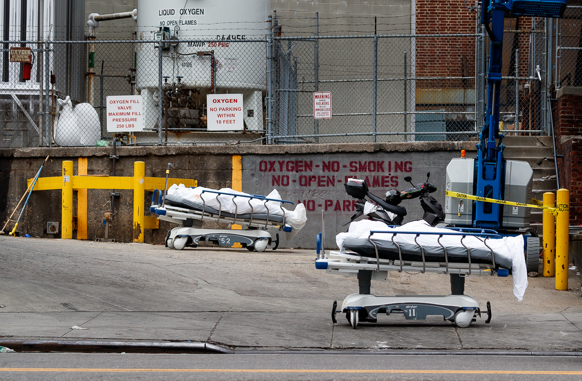 Two bodies on hospital trolleys are prepared for storage in a mobile morgue, put in place due to a lack of space at the Brooklyn Hospital Center. [Justin Lane/EPA]