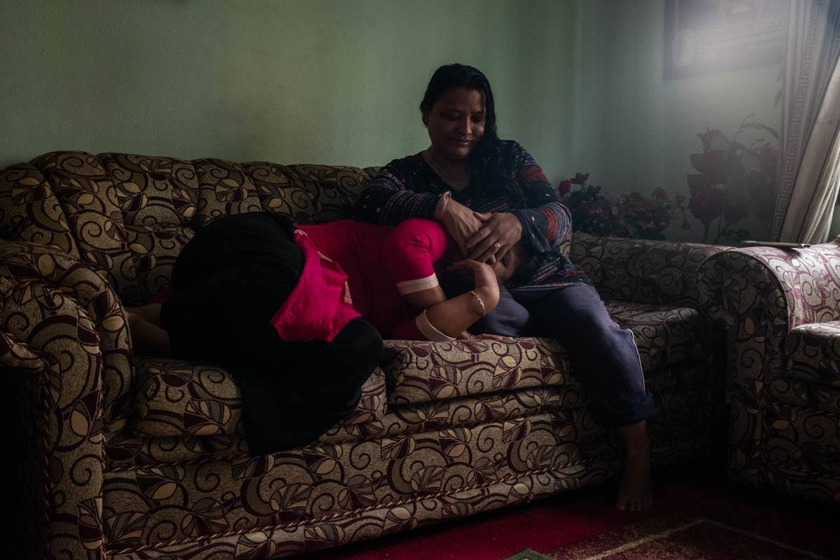 Sunita Danwuar, right, covers the face of 30-year-old Tina*, at the Danwuars' home in Kathmandu. Tina survived rape, abuse and enslavement in Kuwait, and Sunita was rescued after being kidnapped from her family at 14 and raped for four years in a brothel in Mumbai. She now spearheads the fight against the trafficking of women from Nepal. The two women are a source of support to each other and other survivors. [Violeta Santos Moura/Al Jazeera]