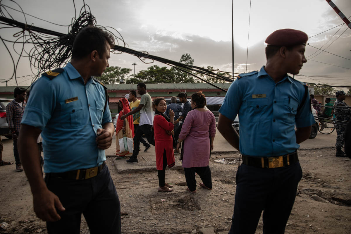 Two police officers, far left and far right, stand near anti-trafficking NGO border monitors, centre, with whom they coordinate efforts to prevent human trafficking from Nepal into India in the Nepalese border city of Bhairahawa. [Violeta Santos Moura/Al Jazeera]