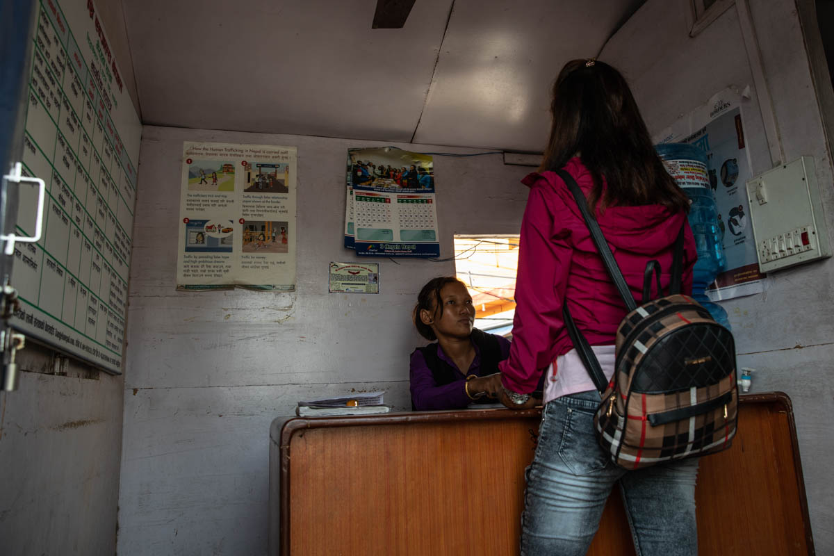 Danu Thapa, 24, an anti-trafficking NGO border monitor, questions a girl in an NGO booth after stopping her at the border pass in Bhairahawa. Poverty is the most common reason girls agree to be trafficked. But lack of human rights protections, political instability, conflict, natural disasters, illiteracy and corruption catalyse the phenomenon. [Violeta Santos Moura/Al Jazeera]