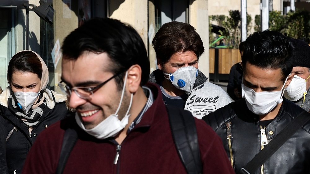 People wearing face masks walk on a sidewalk, in downtown Tehran, Iran, Monday, March 2, 2020. A member of a council that advises Iran's supreme leader died Monday after falling sick from the new coro