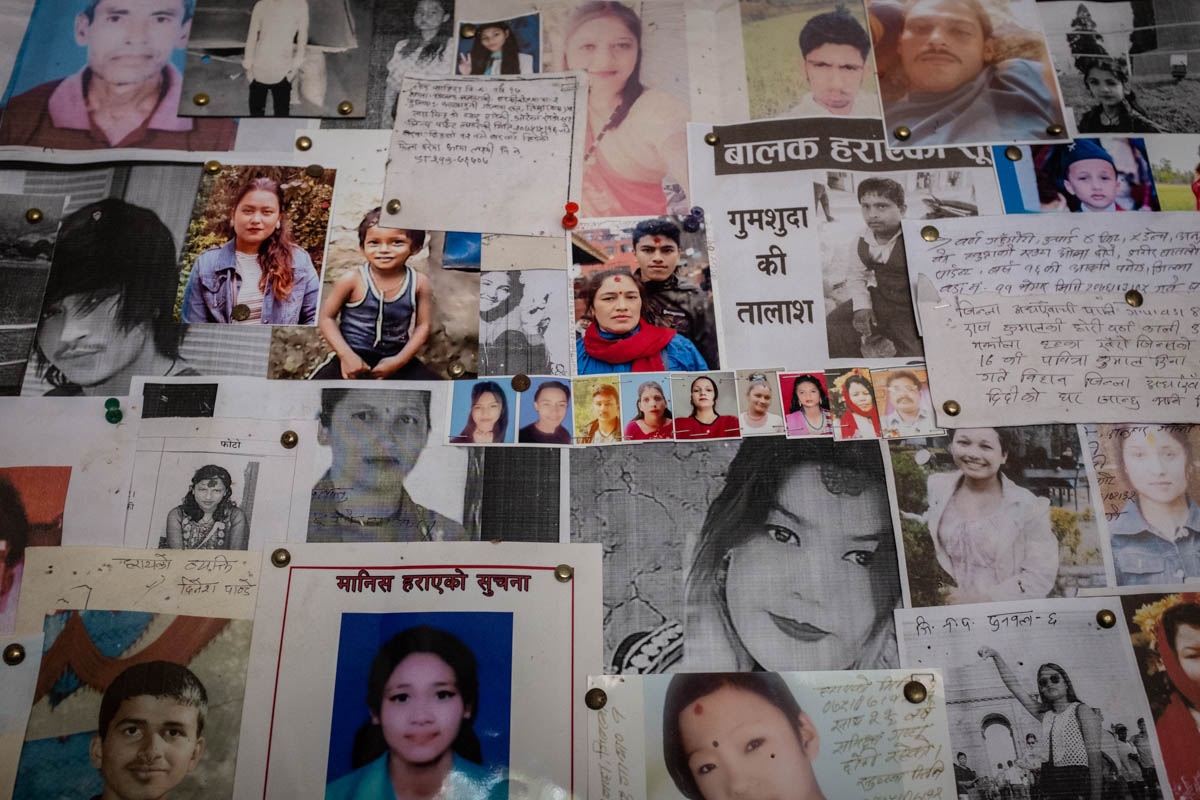 Photos, messages and descriptions of missing men, women and children - many thought to have been trafficked - fill a board at the Nepal-India border police station in Bhairahawa. A 2019 report by Nepal's National Human Rights Commission confirms that many missing children and adults end up trafficked. [Violeta Santos Moura/Al Jazeera]