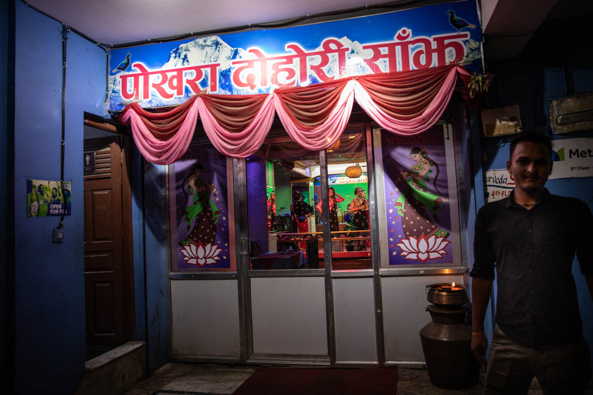 A patron (right) is seen at the entrance of a type of singing bar and restaurant known as 'dohori' where Nepali music and dance, both traditional and modern, is performed, in Kathmandu, Nepal. [Violeta Santos Moura/Al Jazeera]