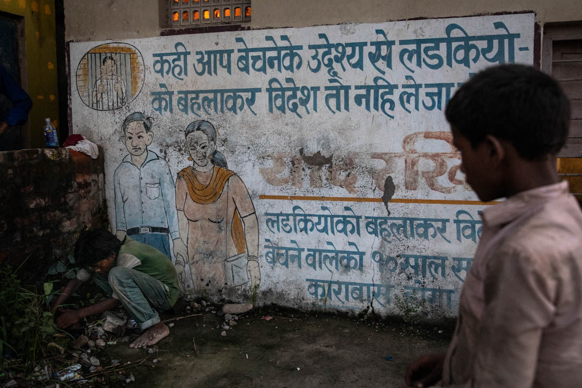 Two boys play beside a mural on the border between India and Nepal which warns women travellers of the risks of trafficking. It specifically cautions that accompanying someone who promises a job across the border could, in reality, be a ruse intended to sell them. However, high levels of illiteracy (more than 40 percent among women in Nepal) mean that not everyone will get the message. [Violeta Santos Moura/Al Jazeera]