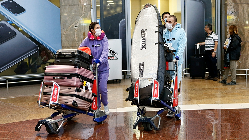 Passenger wearing protective face masks arrive from Shenzhen in China, at the OR Tambo International Airport in Johannesburg, on March 2, 2020 amid concerns about the spread of the COVID-19 epidemic c