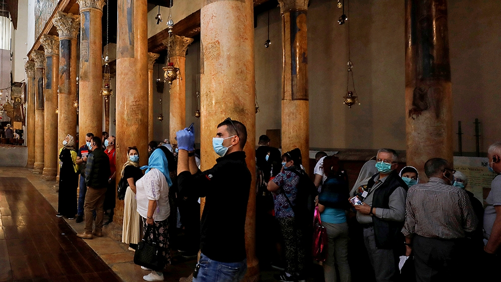 A visitor wearing a mask as a preventive measure against the coronavirus takes pictures in the Church of the Nativity in Bethlehem in the Israeli-occupied West Bank March 5, 2020. REUTERS/Mussa Qawasm