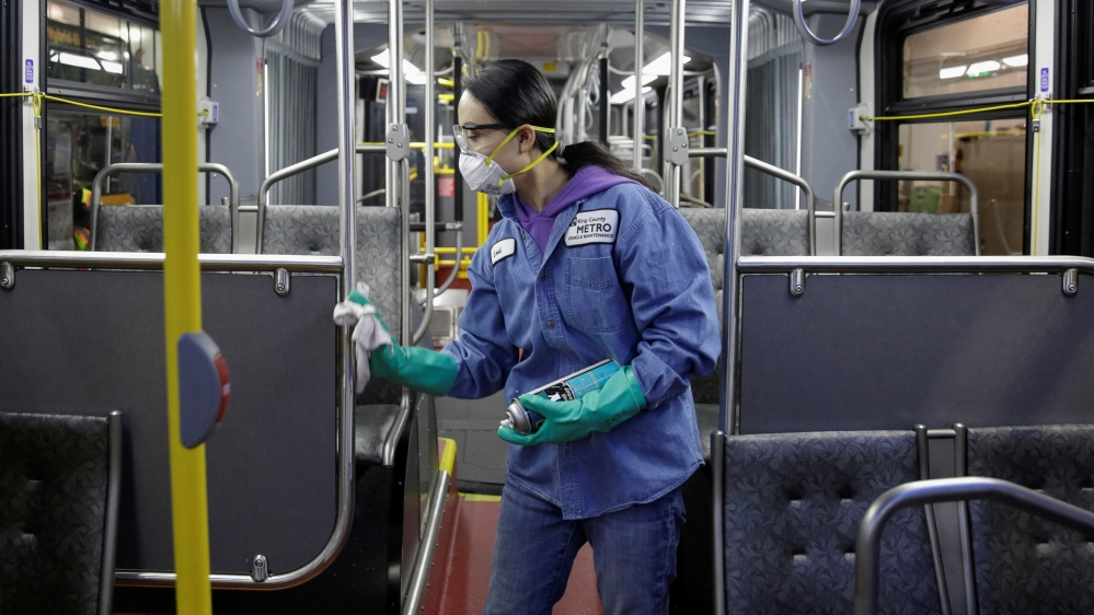 FILE PHOTO: Vehicle Maintenance Utility Service Worker Thiphavanh 'Loui' Thepvongsa wipes down an off-duty bus with a disinfectant during a routine cleaning at the King County Metro Atlanti