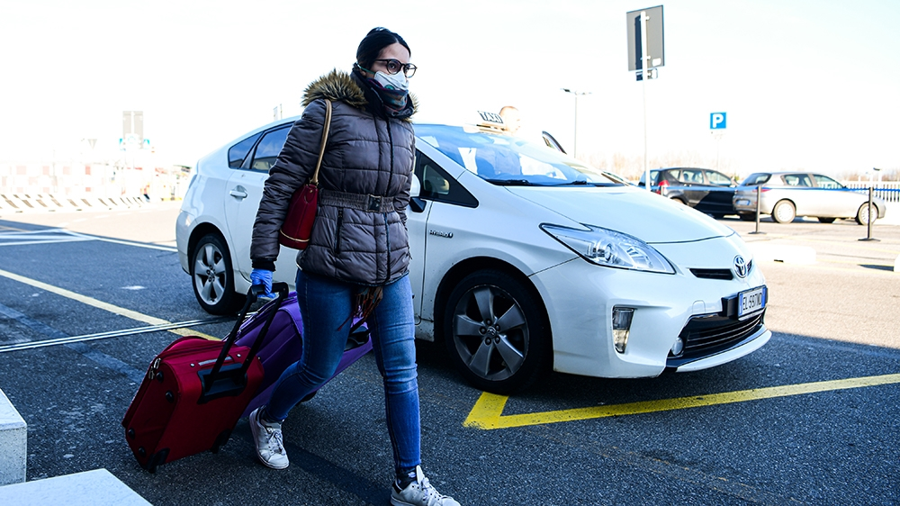 A passenger wearing a protective face mask, amid concerns about the COVID-19 outbreak, walks in Linate Airport in Milan on March 8, 2020, after millions of people were placed under forced quarantine i