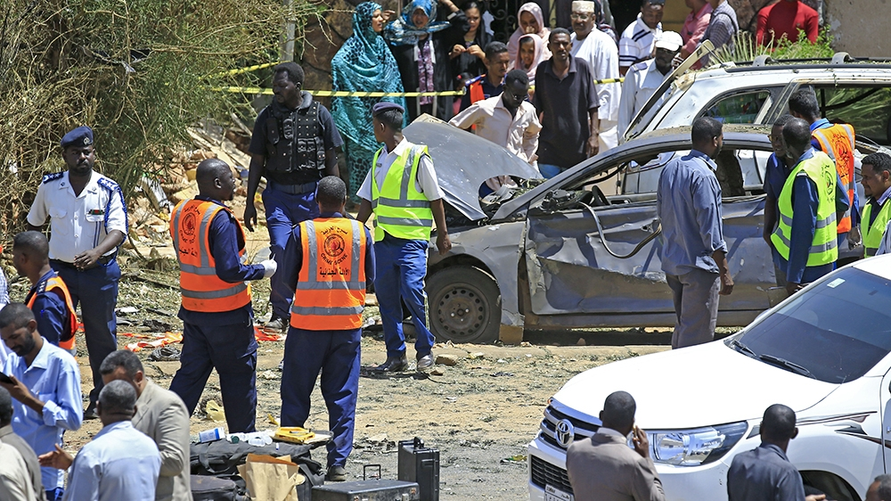 Sudanese rescue teams and security forces gather next to damaged vehicles at the site of an assassination attempt against Sudan's Prime Minister Abdalla Hamdok, who survived the attack with explosives