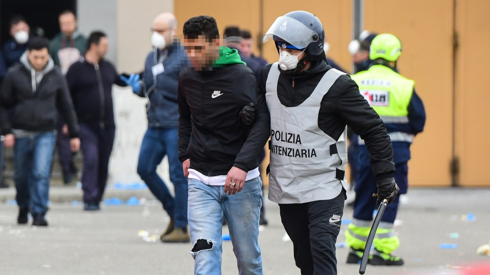 A prison guard wearing a respiratory mask (R) escorts an inmate across a yard of the Sant'Anna prison in Modena, Emilia-Romagna, as some inmates are transfered from a building to another, in one of It