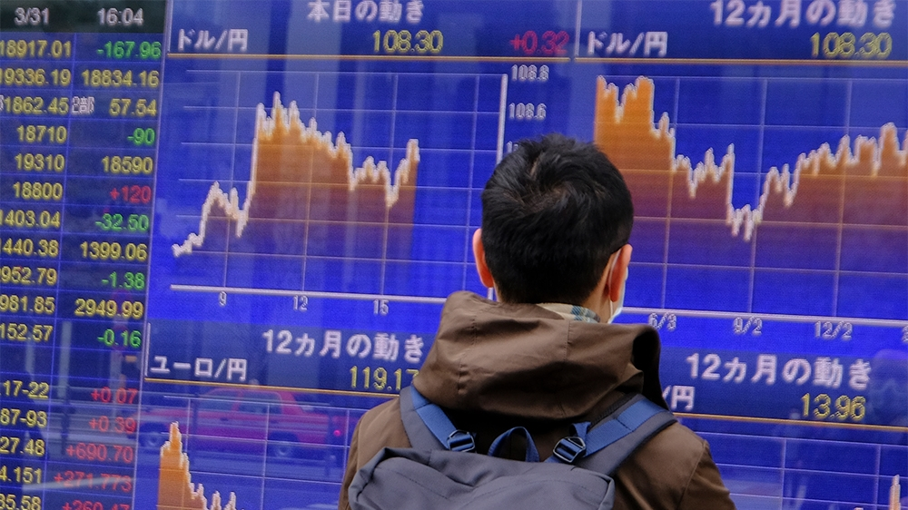 A man looks at movements of the foreign exchange rate against the US dollar (upper) in Tokyo on March 31, 2020. - Tokyo shares closed lower on March 31 in volatile trade, as investors remained nervous