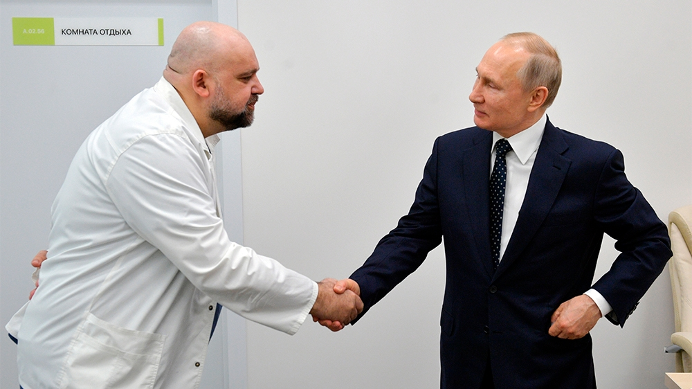 FILE In this file photo taken on Monday, March 23, 2020, Russian President Vladimir Putin, right shakes hands with the hospital's chief Denis Protsenko during his visit to the hospital for coronavirus