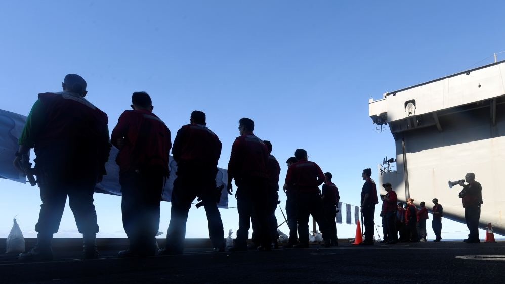 U.S. Navy sailors participate in a small arms qualification aboard the aircraft carrier USS Theodore Roosevelt