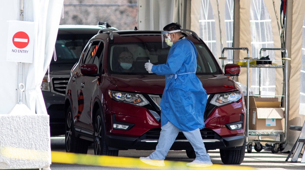 A frontline healthcare worker attends people at the Etobicoke General Hospital drive-thru COVID-19 assessment centre as the number of coronavirus disease (COVID-19) cases continue to grow, in Toronto,