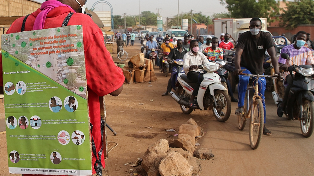 epa08331382 A man from Burkina Faso wears an information poster and uses a microphone on a roadside to deliver a public service announcement as part of an awareness campaign over the coronavirus SARS-