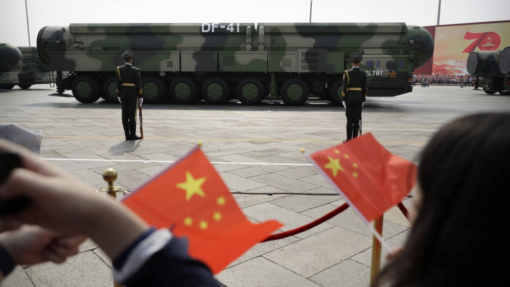 Spectators wave Chinese flags as military vehicles carrying DF-41 ballistic missiles roll during a parade to commemorate the 70th anniversary of the founding of Communist China in Beijing, Tuesday, Oc