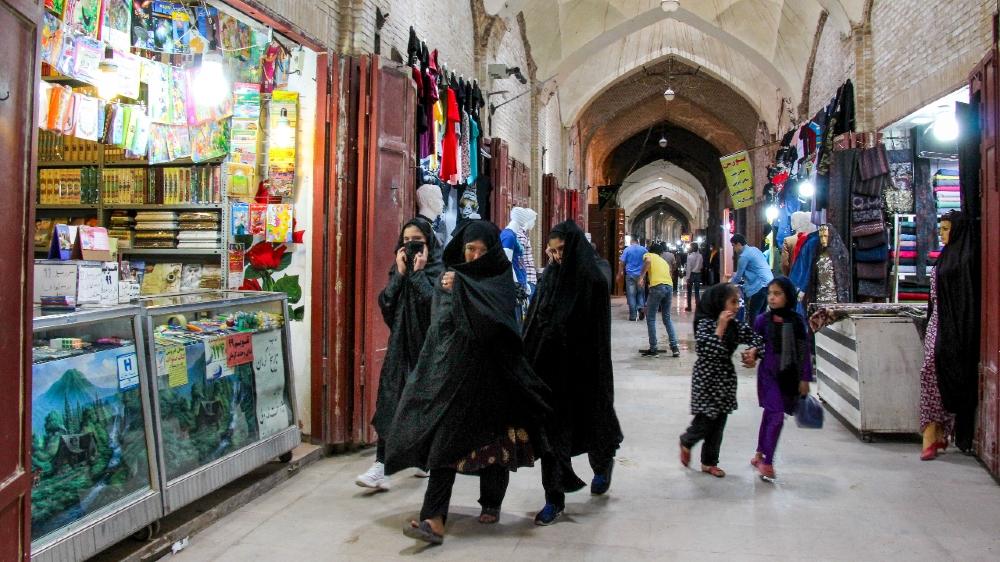 news  world news  bbc news  cnn news  sport news IRAN-HEALTH-VIRUS  Iranians, some wearing personal protective equipment, walk past shops in the southeastern city of Kerman on April 11, 2020, amid the coronavirus (COVID-19) pandemic.