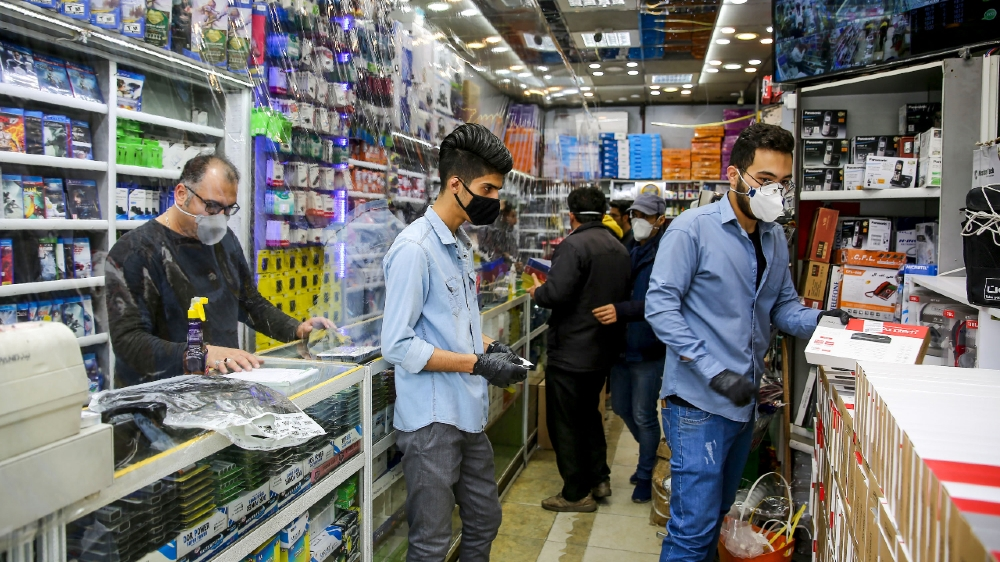 news  world news  bbc news  cnn news  sport news IRAN-HEALTH-VIRUS  Iranian men, wearing personal protective equipment, are pictured at an electronics shop in Mashhad on April 11, 2020, amid the coronavirus (COVID-19) pandemic.