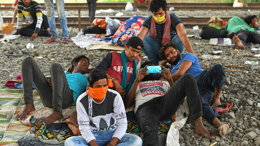 Migrant labourers watch a movie on their mobile phone while resting under a bridge during a government-imposed nationwide lockdown as a preventive measure against the spread of the COVID-19 coronaviru