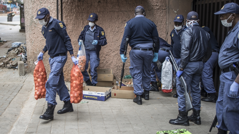 South African police officers confiscate unlawfully sold items at an informal trading post in Hillbrow, Johannesburg, on March 28, 2020 during the second day of the Country's lockdown. South Africa c