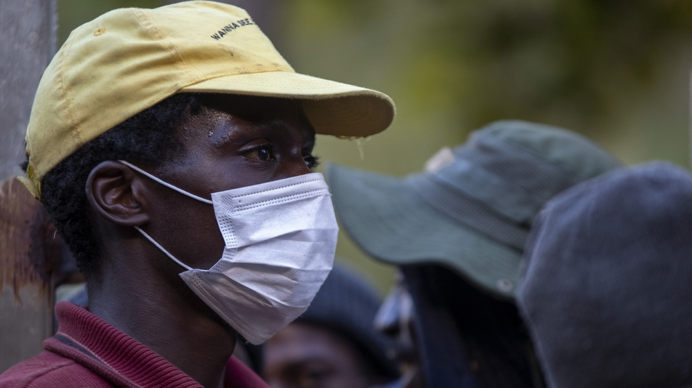 A man wearing face masks to protect herself against coronavirus, mends the gate as homeless people are queuing for a meal and a shelter in Hillbrow, Johannesburg, South Africa, Friday, March 27, 2020.