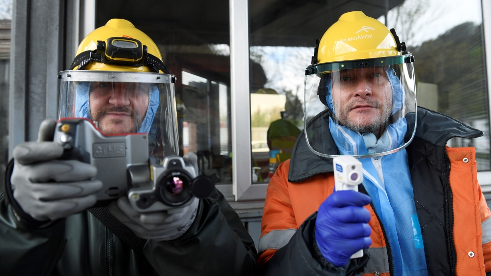 Workers from the multinational ArcelorMittal pose with a thermal camera and a digital thermometer with which they use to take the temperature of personnel entering a factory, to help combat the spread
