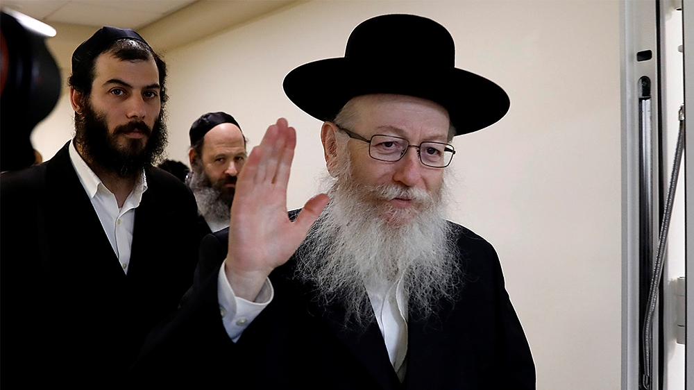 Israeli Health Minister Yakov Litzman, a rabbi from the United Torah Judaism party, waves to journalists after handing in his resignation to Prime Minister Benjamin Netanyahu, during the weekly cabine
