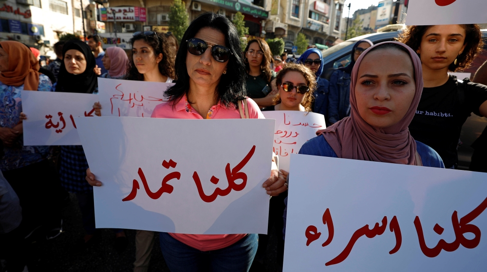 Demonstrators hold signs during a protest demanding legal protection for women, in Ramallah in the Israeli-occupied West Bank September 4, 2019. REUTERS/Mohamad Torokman