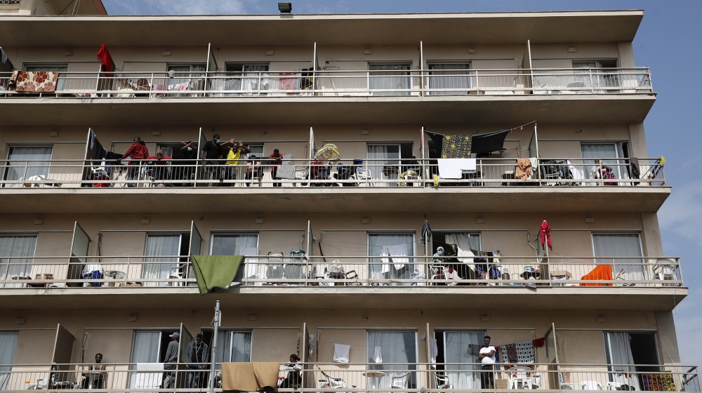 Migrants gather on their balconies at a hotel in Kranidi town about 170 kilometers (106 miles) southwest of Athens, Tuesday, April 21, 2020. The heads of Greece's pandemic response effort are visiting