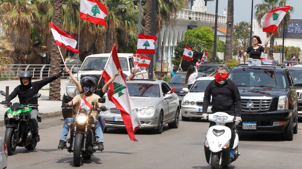 Anti-government demonstrators wave Lebanese flags as they protest in their cars, amid a countrywide lockdown to combat the spread of the coronavirus disease (COVID-19), in Beirut