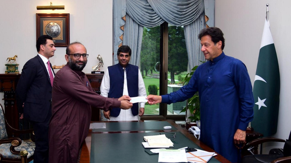 Pakistani Prime Minister Imran Khan receives a cheque from Head of the Edhi Foundation Faisal Edhi, for the Prime Minister's coronavirus disease (COVID-19) relief fund at the Prime Minister House