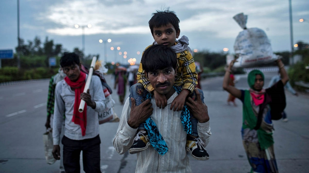 Dayaram Kushwaha, a migrant worker, carries his 5-year-old son, Shivam, on his shoulders as they walk along a road to return to their village, during a 21-day nationwide lockdown to limit the spreadin