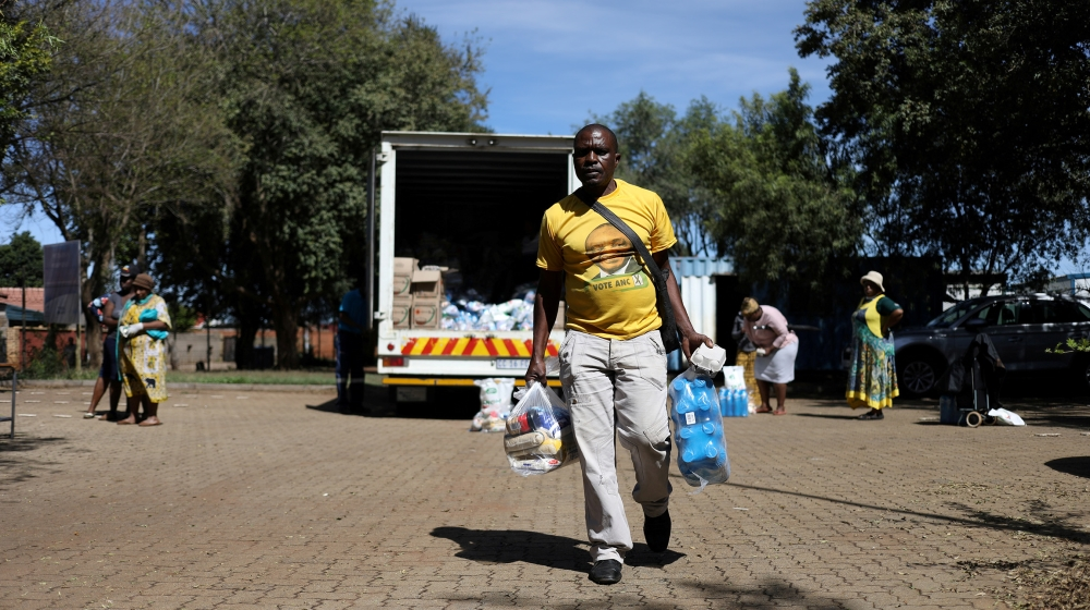 A man wearing a t-shirt with the face of South Africa's president, Cyril Ramaphosa leaves as people distribute food parcels prepared by the local government to vulnerable residents during a 21-day loc