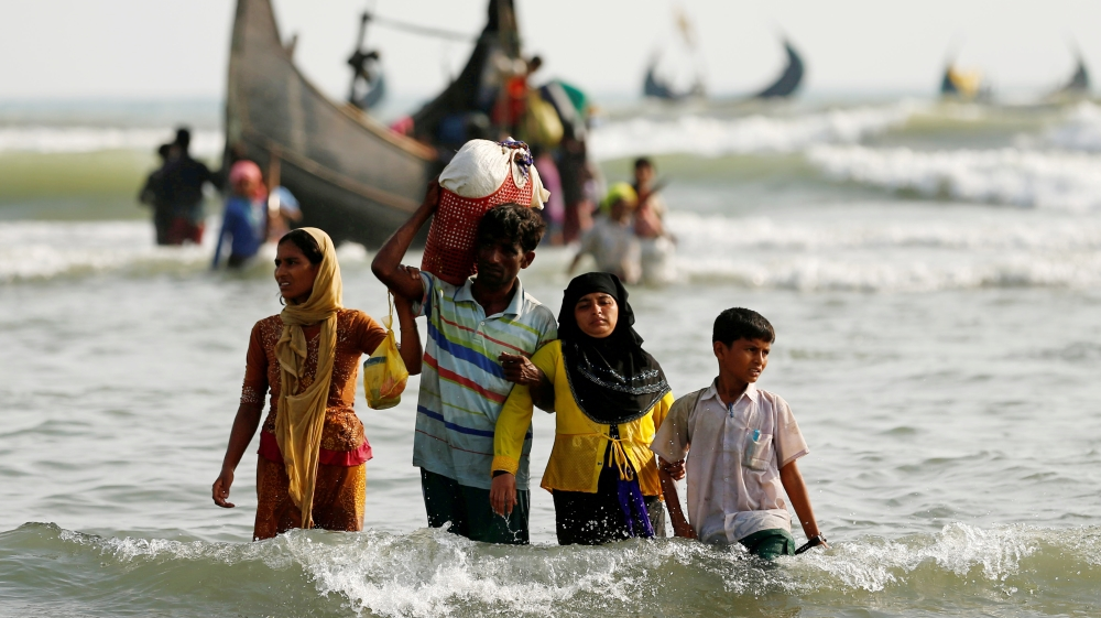 Rohingya refugees walk to the shore with his belongings after crossing the Bangladesh-Myanmar border by boat through the Bay of Bengal in Teknaf