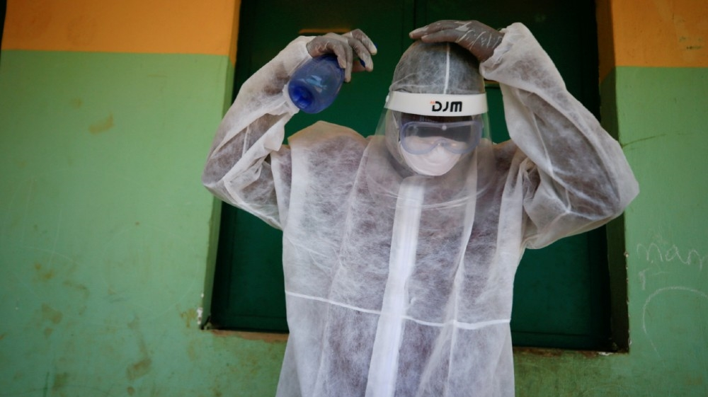 A health worker sprays his headset during a community testing exercise, as authorities race to contain the spread of the coronavirus disease (COVID-19) in Abuja, Nigeria April 16, 2020.