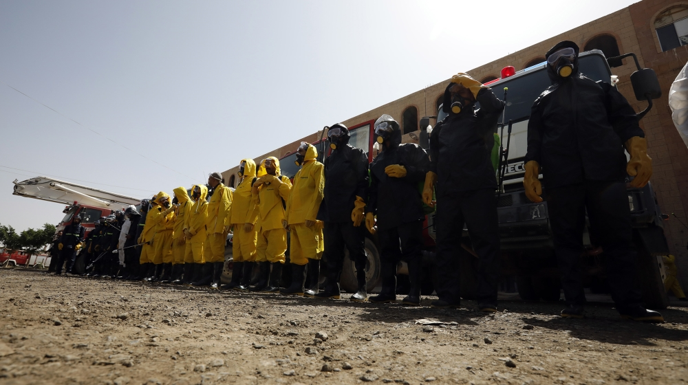 Staff of the Yemeni civil defense wearing protective gear, prepare to spray disinfectant during a demonstration of an anti-proliferation training of the SARS-CoV-2 coronavirus, in Sanaa, Yemen, 12 Apr