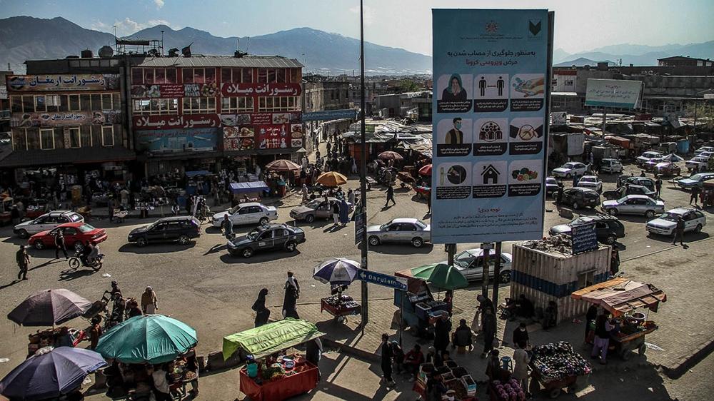A sign with anti-coronavirus measures over a busy bazaar in Kabul [Agnieszka Pikulicka-Wilczewska/Al Jazeera]