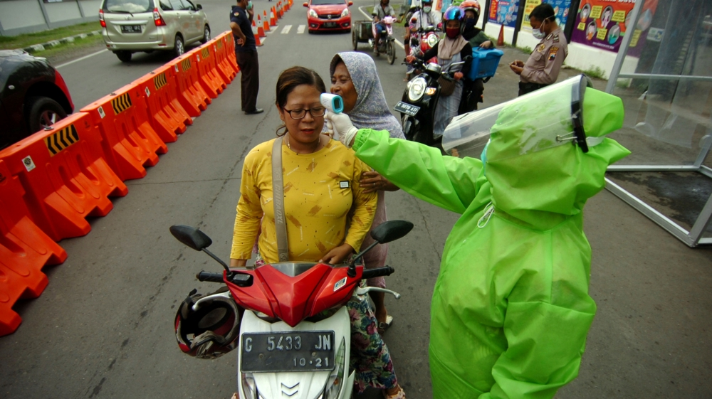 A medical officer wearing a protective suit checks a woman with a thermal scanner amid the coronavirus disease (COVID-19) outbreak in Tegal