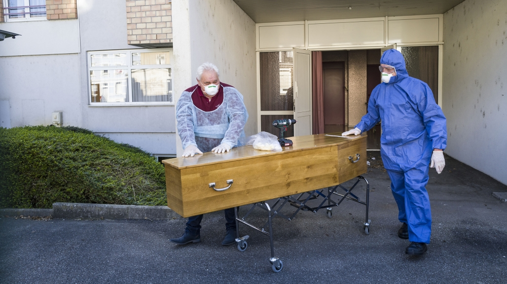 Employees of the Lantz funeral company, wearing protections, pull the coffin of a victim of the COVID-19 of an EHPAD (Housing Establishment for Dependant Elderly People), in Mulhouse, eastern France,
