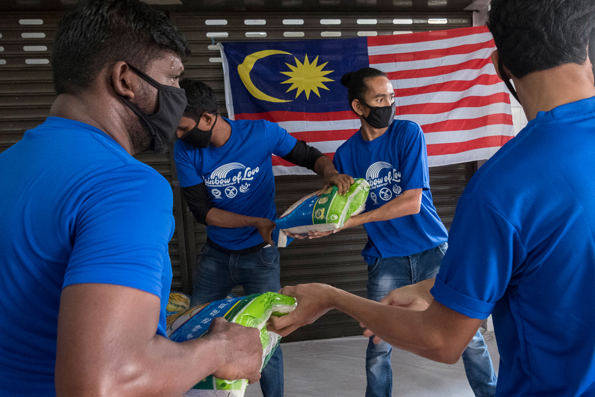 Volunteers help unload a lorry carrying dry food and pack the various foods into ready-to-distribute bags at a refugee community centre on the outskirts of Kuala Lumpur. [Alexandra Radu/Al Jazeera]