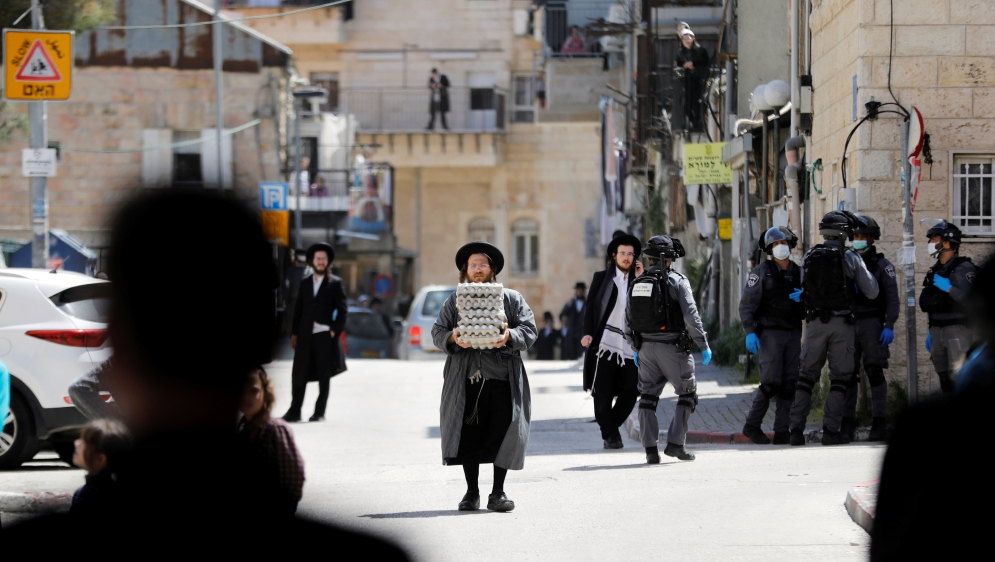 An ultra-Orthodox Jewish man carries trays of eggs as Israeli police patrol nearby to enforce government restrictions set in place to curb the spread of the coronavirus (COVID-19), in Mea Shearim neig