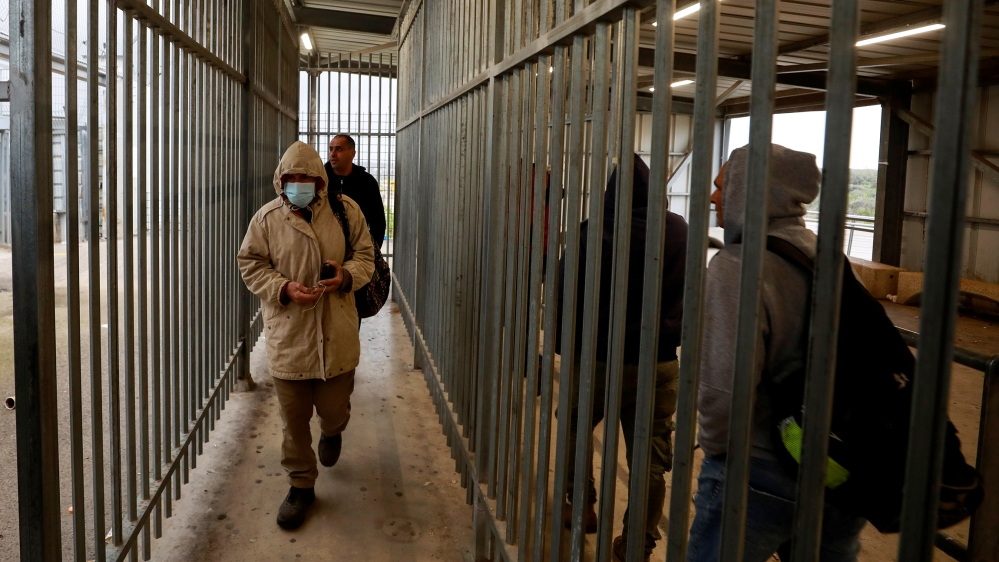 Palestinians working in Israel head to work through an Israeli checkpoint as the Palestinian Authority ordered them to stay at their workplaces over concerns of the spread of coronavirus disease, near