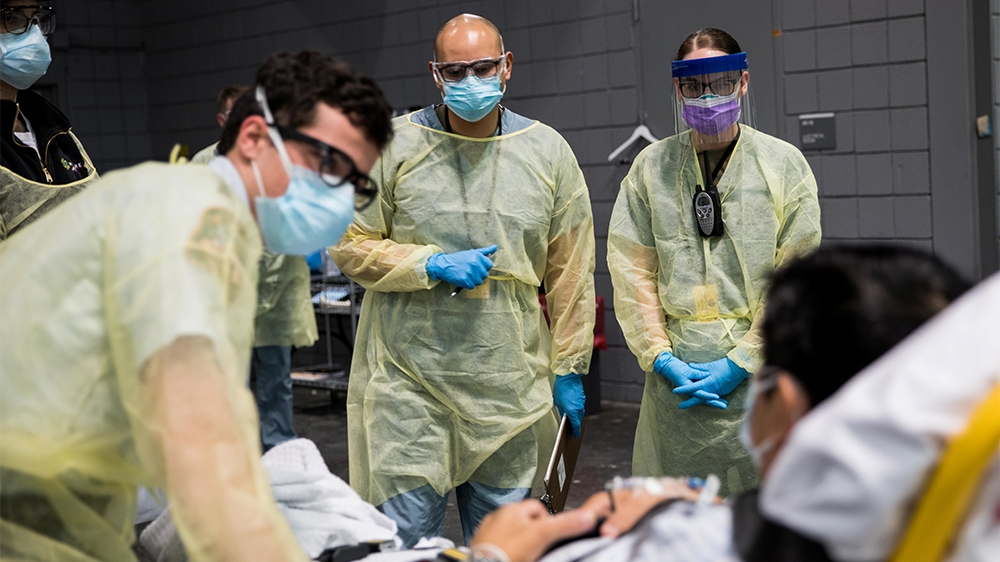 Soldiers assigned to Javits New York Medical Station conduct check-in procedures on an incoming coronavirus disease (COVID-19) patient with local emergency workers in the facility's medical bay in New