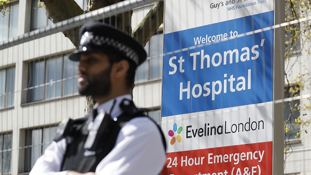Police officers stand in front of barriers erected outside St Thomas' Hospital in London on April 6, 2020. - British Prime Minister Boris Johnson was in hospital on Monday undergoing tests after suffe