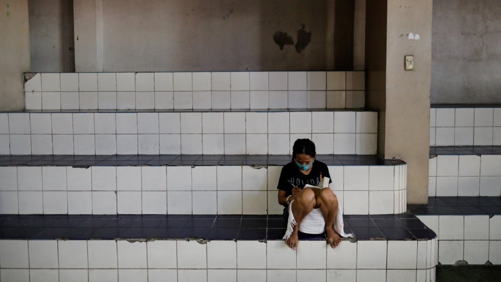 A woman wearing a protective face mask reads the Bible in a gymnasium which turned into a shelter for the homeless following the enforcement of a community quarantine in Manila