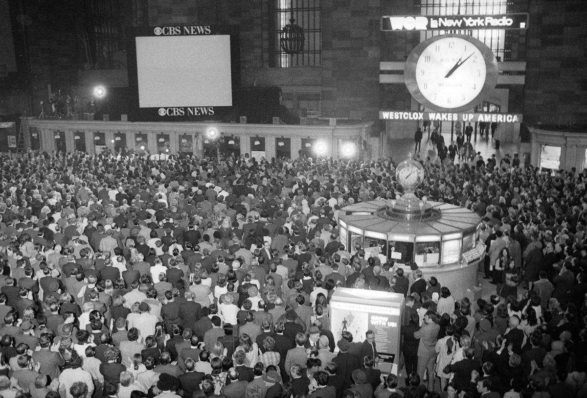 වේලාව ප.ව. 1.00 ඊඑස්ටී වන අතර, 1970 අප්රියෙල් 17 වන දින නිව් යෝර්ක් නගරයේ ග්රෑන්ඩ් සෙන්ට්රල් ස්ටේෂන් හි රූපවාහිනී තිරය දෙස සියලු දෙනාම අවධානය යොමු කර ඇති අතර පැසිෆික් සාගරයේ ඇපලෝ 13 ගගනගාමීන් ආරක්ෂිතව ගොඩබසිනු ඇතැයි බලා සිටිති.  [ජේ ස්පෙන්සර් ජෝන්ස් / ඒපී ඡායාරූපය]