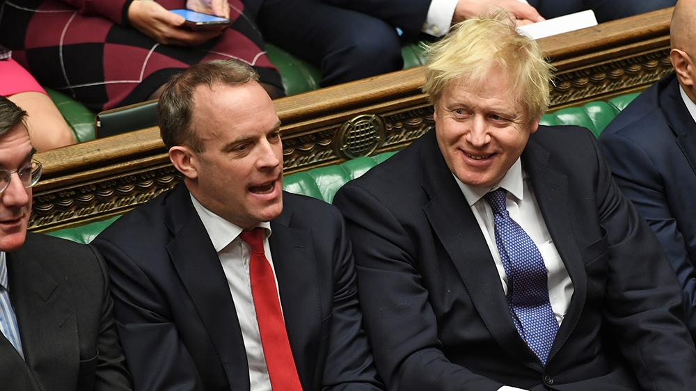 A handout photograph released by the UK Parliament shows Britain's Prime Minister Boris Johnson (C) smiling beside (L-R) Britain's Leader of the House of Commons J