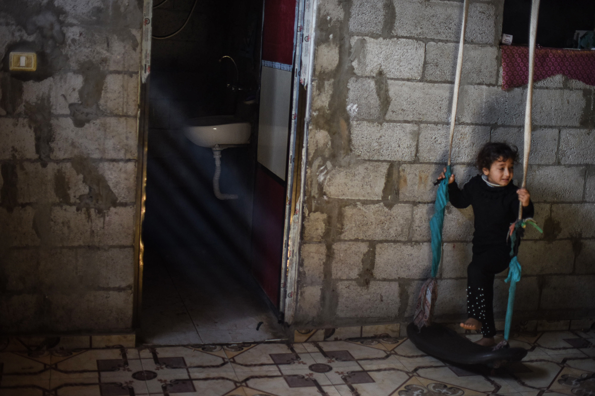 A girl on a swing inside her house in Khan Younis refugee camp. Parents are trying to provide entertainment inside their homes to ensure children do not play in the streets. [Abed Zagout/ICRC]