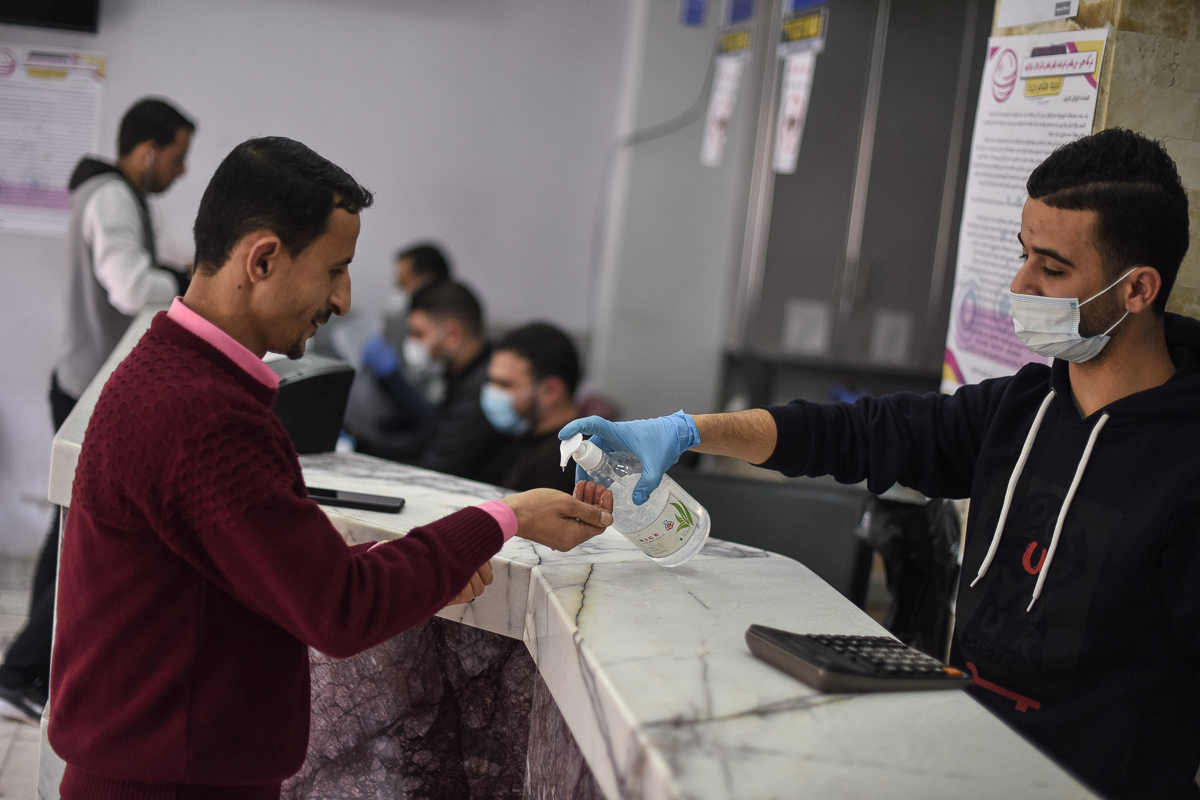 An employee at a currency exchange gives a customer a squirt of hand sanitiser, now a common ritual in Gaza's stores. [Abed Zagout/ICRC]
